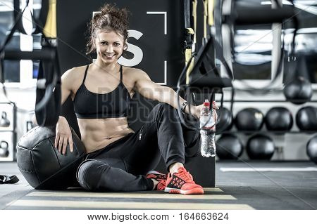 Charming woman with curly hair sits on the floor in the gym on the background of the partition. She wears dark sportswear with red sneakers. Girl leans on the black ball and holds a bottle of water.