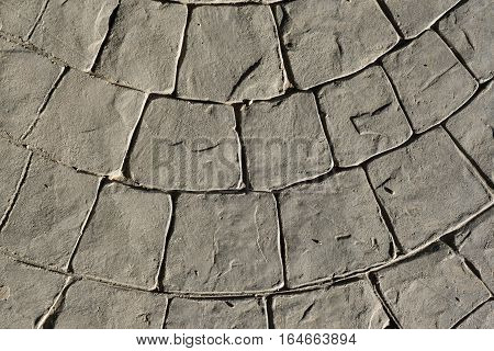 Gray stamped concrete pavement outdoor, mimics cobblestones circular pattern with waves, flooring exterior, decorative appearance colors and textures of paving cobble stone, top view