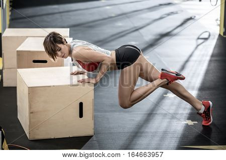 Sexy girl leans on the wooden box with her hands and holds the left leg in the air in the gym. She wears a black shorts, red top and sneakers, gray sleeveless. Daylight shines on her from behind.