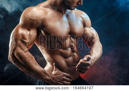 Unrecognizable Strong bald bodybuilder with six pack. Bodybuilder man with perfect abs, shoulders, biceps, triceps and chest, personal fitness trainer flexing his muscles in blue, red smoke