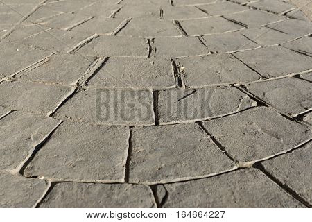 Gray stamped concrete pavement outdoor, mimics cobblestones circular pattern with waves, flooring exterior, decorative appearance colors and textures of paving cobble stone, perspective
