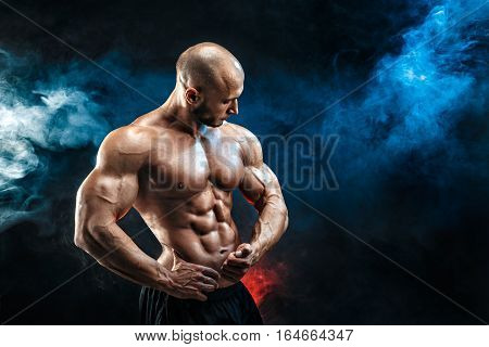 Strong bald bodybuilder with six pack. Bodybuilder man with perfect abs, shoulders, biceps, triceps and chest, personal fitness trainer flexing his muscles in blue, red smoke