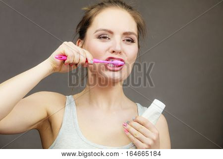 Woman holding brush and tooth paste for teeth cleaning. Happy funny smiling girl with toothbrush. Oral hygiene. Studio shot dark background