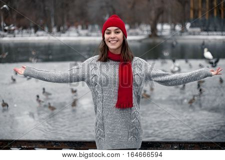 Girl in red hat and scarf walking in winter park near lake. She is smiling and very pleased and happy.