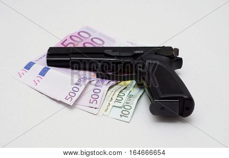 Pistol is lying on a lot of euro banknotes