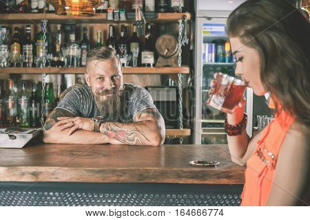 Beautiful girl is drinking a cocktail with ice vapor in the bar. Nightclub. Handsome bartender working at background. Young woman looking at camera