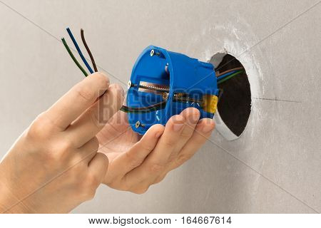 hands of electrician installing plastic outlet box for electric wall sockets