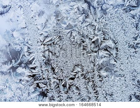 intricate, delicate patterns of frost crystals on a sparkling glass