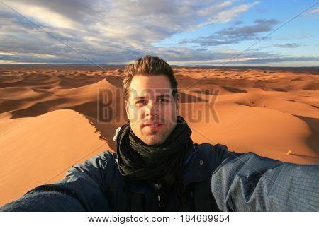 Male solo traveler taking selfie at dunes in Sahara desert, Morocco.