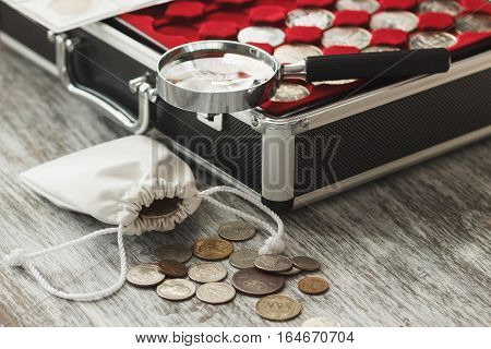 Different Collector's Coins With A Magnifying Glass