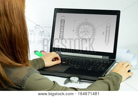 Young woman using CAD system in front of a laptop back view