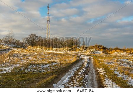 Winter landscape with country road leading to cellular radio tower in Ukrainian rural area