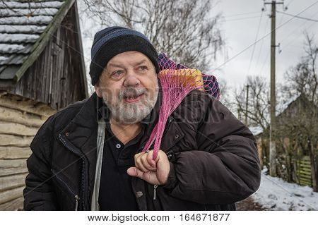 Outdoor portrait of positive Ukrainian peasant standing on a rural village street and taking string-bag with household things