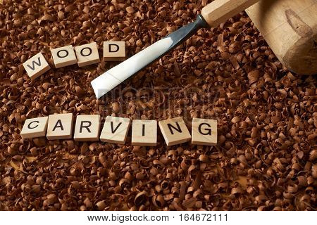 wood carving word writen with letters on wood chips with chisel and a mallet