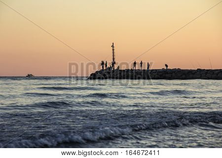 Sunset on Tyrrhenian sea, view of breakwater, fishermen silhouettes, harbor and seacoast of Terracina, Lazio, Italy