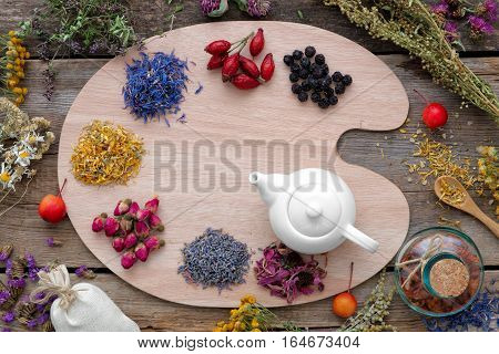 Healing herbs on wooden palette and tea kettle top view. Herbal medicine concept.