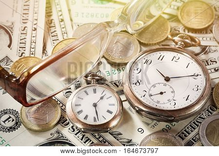 Time is money finance concept with old vintage clocks, dollar bills, euro coins and glasses.