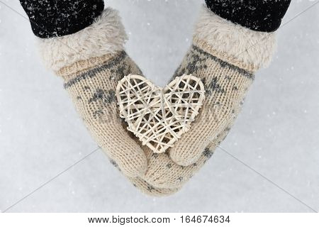 Woman holding white rattan heart on winter snow background, close up. Valentines Day concept.