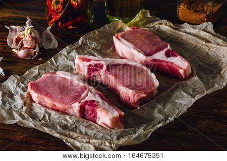 Three Pork Loin Chops on Paper with Spices