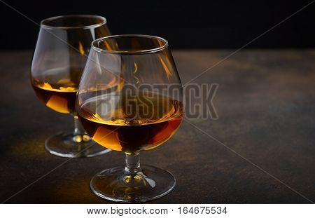 Glass of brandy or cognac on the old rusty background, selective focus, horizontal
