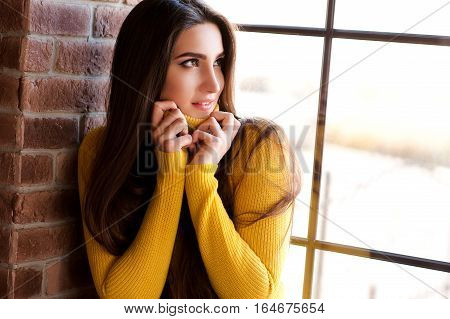 Beautiful brunette girl 20-24 year old wearing yellow knitted sweater sitting on windowsill looking at window in room. Looking away. Smiling young adult. 20s. Winter season.