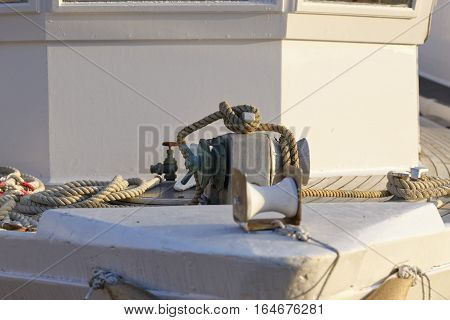 detail of a winch on top a white fishing boat
