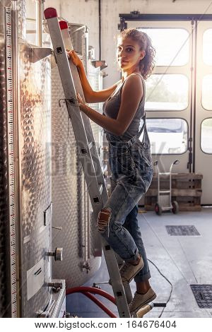 Female Winemaker Controls The Quality Of Wine On Ladder Over Tank