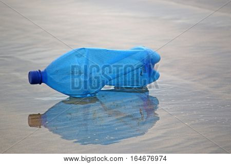 plastic bottle lying reflected on a beach