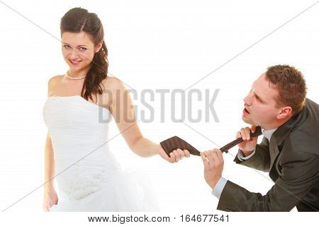 Relationship command concept. Dominant bride wearing wedding dress pulling groom tie isolated.