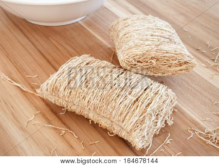 Shredded wheat cereal with white bowl in background.