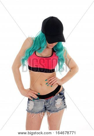 A slim young woman standing in front in ripped shorts sports bra and a cap with long blue hair isolated for white background.