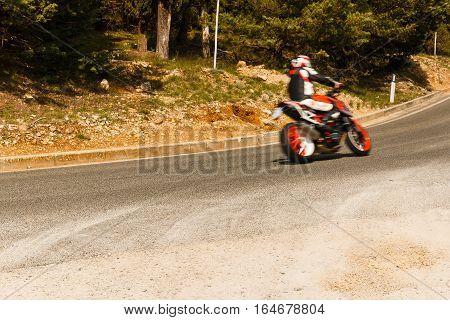 Motor bike racing through the corner of the road motion unsharpness