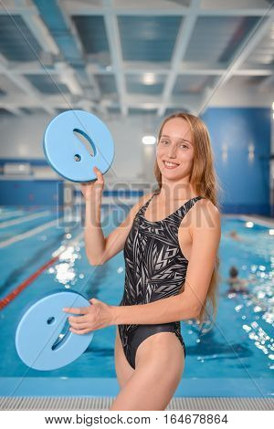 Young Happy Woman juggling with floating boards near swimming pool.
