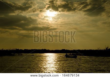 ship at sunset on a lake in Indochina, Cambodia
