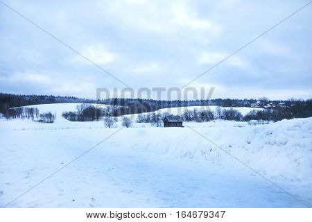 Wooden shed stands in the middle snow, snow-covered hills behind, the forest and the village