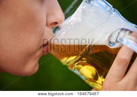 Woman drinking beer with beer mug close up