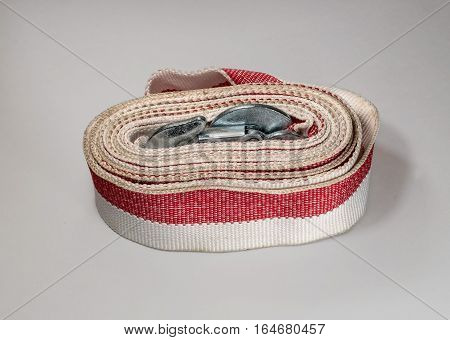 Tow rope to the car on a light background. Rope folded in circle hooks are inside the coil.