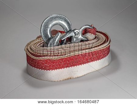 Tow rope to the car on a light background. Rope folded in circle hooks are inside the coil and half protruding.