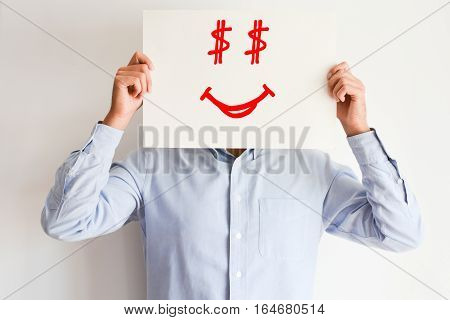 Businessman holding a cardboard sign with a smiling face, having dollar sign eyes, suggesting payday concept