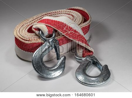 Tow rope to the car on a light background. Rope folded in circle hooks are removed to the outside coil.