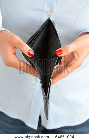 Woman holding an empty wallet suggesting bankruptcy