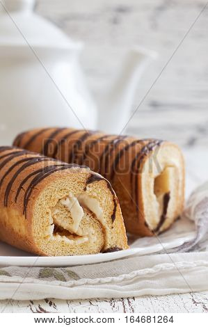 Sweet swiss rolls (roulade) with white cream served on white plate. Copy space