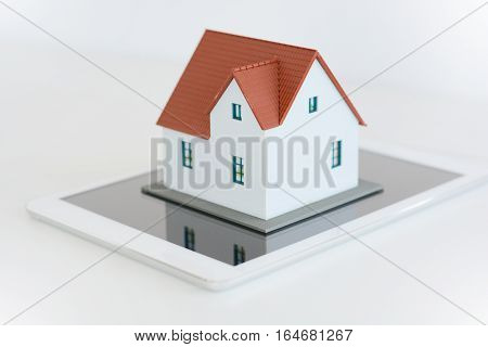Digital tablet and house model on white background