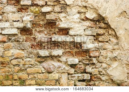 Damaged brick wall. Old bricks background. Centuries turned beauty into ruins.