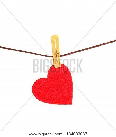 Red heart from dense fabric on a clothespeg on a rope. It is isolated on a white background