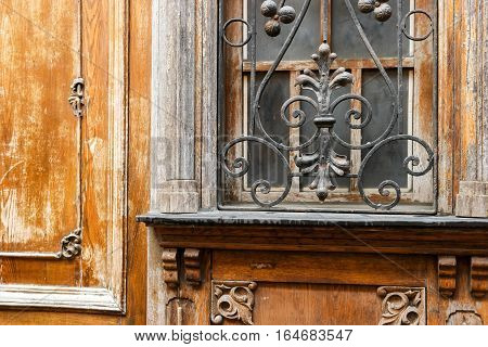 Old window with wrought iron. Aged wood with ornament. History of architecture.
