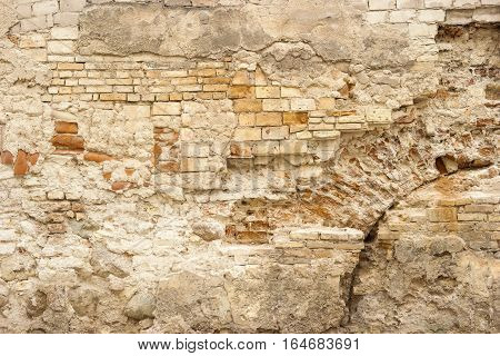 Aged wall of bricks. Old damaged cement. Castles will turn into ruins.