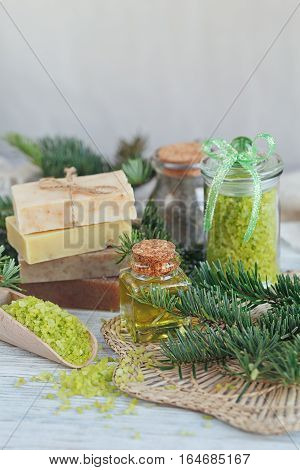 Natural sea salt and handmade soap with branch of pine on white wooden background. SPA concept.