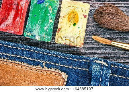 Blue jeans stitched edge, watercolors and paint brushes on the wood. Concept of handicraft background. Macro view and Macro view