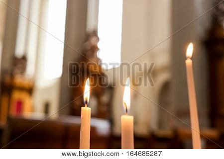 Three burning candles. Church candles on blurred background. Pray in the silence.